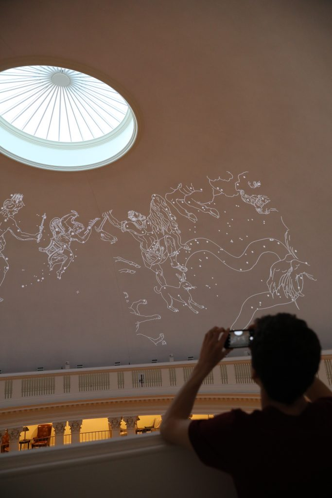 Planetarium team member takes a cellphone picture of the constellation illustration projected onto the ceiling.