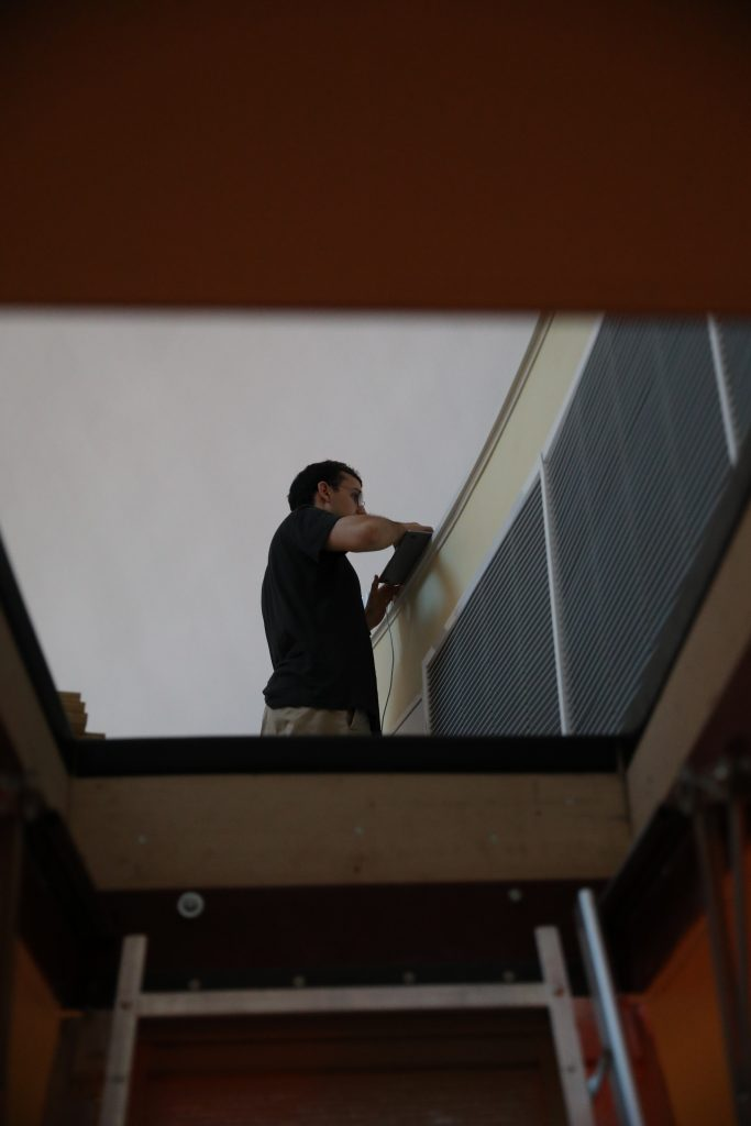 Planetarium team member seen looking upward through window.